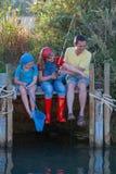 Farsa och ungar som har roligt fiske royaltyfria foton