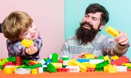 Farsa och unge att bygga plast- kvarter Barnav?rdutveckling Familjfritid Fadersonlek Fader och son att skapa arkivbilder