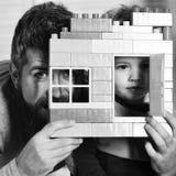 Farsa och unge med skinnet bak byggnadsväggen som göras av plast- kvarter Fader och son med stillhetframsidor bak färgrika tegels Fotografering för Bildbyråer