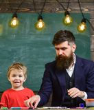 Farsa och unge som har gyckel på konstgrupp Pappa och son som tillsammans målar Arkivbild