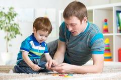 Farsa och unge som hemma spelar leksaker Arkivfoto