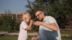 Farsa som ger dricksvatten till hans son i trädgård pojke som dricker little vatten arkivfilmer