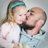 Farsa som ger hans dotter en kyss på kinden Royaltyfri Fotografi