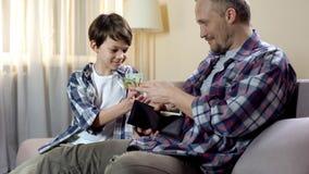 Farsa som ger kassa från plånboken till sonen för nya leksaker, barnfickpengar, finanser royaltyfri foto