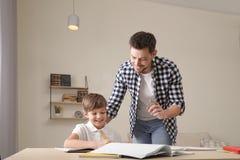 Farsa som hj?lper hans son med skolauppgift arkivbild