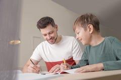 Farsa som hj?lper hans son med skolauppgift arkivfoton
