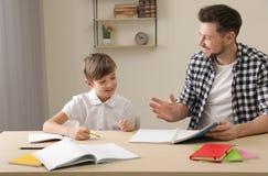 Farsa som hj?lper hans son med skolauppgift arkivbilder