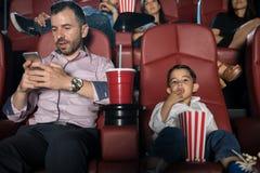 Farsa som kontrollerar hans telefon på filmerna Royaltyfri Foto