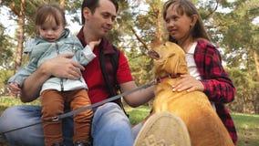 Farsaavelsdjuret med ungar och hunden för går lycklig familj Papins dag Fader och d?ttrar Omsorg och lyftahundkappl?pning husdjur lager videofilmer