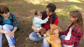 Farsaavelsdjuret med ungar och hunden f?r g?r lycklig familj Papins dag Fader och d?ttrar Omsorg och lyftahundkappl?pning husdjur arkivfilmer