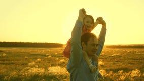 Farsadans p? hans skuldror med hans dotter i sol Faderresor med behandla som ett barn p? hans skuldror i str?lar av solnedg?ngen  arkivfilmer