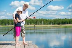 Farsahjälpdotter som fångar fisken med en metspö på floden arkivbild
