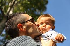 Farsan behandla som ett barn kyssen Arkivfoton