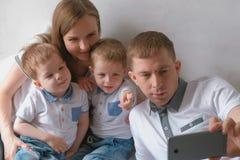 Farsan gör familjselfie på mobiltelefonen Mamman, farsan och broder två kopplar samman små barn royaltyfri bild
