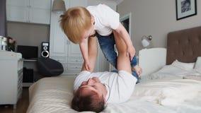 Farsan håller en värdighet ovanför honom som ligger på sängen En pojke i en vit T-tröja skrattar och ler från att spela med hans stock video