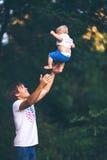 Farsan kastar upp en son uppåt Fotografering för Bildbyråer