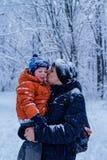 farsan kysser hans son utanför, vinterskogen på bakgrunden och att snöa, lyckligt och glat royaltyfria foton