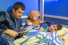 Farsan läser boken till dottern på natten royaltyfri bild