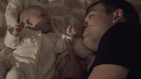 Farsan med älskling behandla som ett barn dottern som ligger på säng arkivfilmer