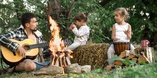 Farsan med döttrar vilar, i att campa på naturen royaltyfri bild
