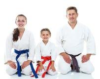 Farsan med hans döttrar i kimonosammanträde i en ritual poserar karate Royaltyfria Bilder