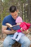 Farsan och behandla som ett barn den läs- bibeln för dottern Arkivfoton