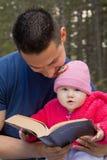 Farsan och behandla som ett barn den läs- bibeln för dottern Arkivbilder