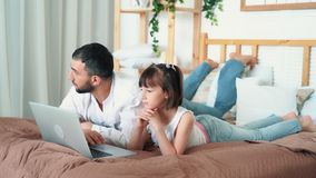 Farsan och det gulliga barnet håller ögonen på den roliga videoen på hemmastadda lögner för bärbar dator på säng, ultrarapid arkivfilmer