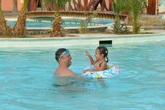Farsan och dottern kopplar av i pöl Royaltyfria Bilder