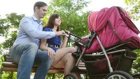 Farsan och mamman sitter på bänk med behandla som ett barn sittvagnen parkerar in, familjferie på fridag i sommaren arkivfilmer