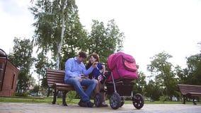 Farsan och mamman sitter på bänk med behandla som ett barn sittvagnen parkerar in, familjferie på fridag i sommaren lager videofilmer