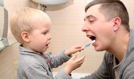 Farsan och sonen borstar deras tänder i badrummet Fader Brushing Teeth till barnet royaltyfri bild