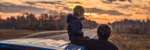 Farsan och sonen vilar på sidan av vägen på en vägtur Vägtur med barnbegreppsBANRET, LÅNGT FORMAT arkivbild