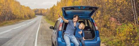 Farsan och sonen vilar på sidan av vägen på en vägtur Vägtur med barnbegreppsBANRET, LÅNGT FORMAT fotografering för bildbyråer