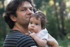 Farsan rymmer en dotter i hans armar för en gå i parkera Vårdagen, familj går i naturen som är solig Fokus på Arkivbild