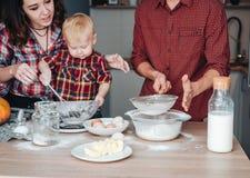 Farsan siktar mjöl i köket fotografering för bildbyråer