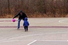 Farsan som undervisar hans 2 år son för att spela basket parkerar på våren royaltyfria bilder