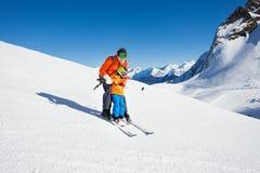 Farsan undervisar den lilla sonen att skida i berg Arkivbild