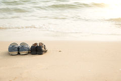 Farther's shoes and son's shoes on thes beac Royalty Free Stock Image