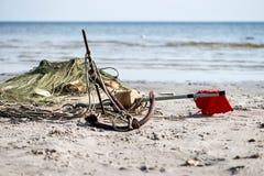 Fartyg ankrar och fisknät i strandsanden Arkivbilder