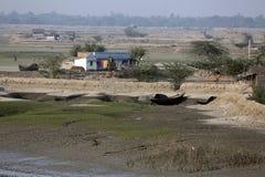 Fartyg av fiskare strandade i gyttjan på lågvatten på flodMalta den near staden på burk, Indien Royaltyfria Bilder
