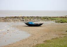 Fartyg av fiskare strandade i gyttjan på lågvatten på kusten av fjärden av Bengal Arkivbild