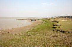 Fartyg av fiskare strandade i gyttjan på lågvatten på kusten av fjärden av Bengal Arkivfoton
