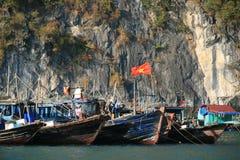 Fartyg förtöjas nära en sväva by i den Halong fjärden (Vietnam) arkivbilder