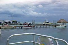 Fartyg förtöjas till flera skeppsdockor i gråambra Caye, som regnmoln samlar i bakgrunden fotografering för bildbyråer