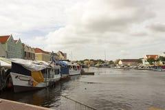 Fartyg förtöjde bak iconic färgrika byggnader av Curacao och den sväva marknaden Arkivfoto