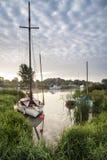 Fartyg förtöjde på flodstrand på soluppgång i bygdlandskap Arkivfoto