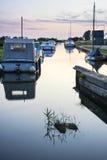Fartyg förtöjde på flodstrand på soluppgång i bygdlandskap Arkivfoton