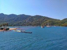 Fartyg, havet, himmel och turister i vatten på flickasand sätter på land Är här den berömda stimen, ett ställe av pilgrimsfärden  Arkivbild