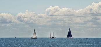 Fartyg i det blåa havet, molnig himmel Arkivbild